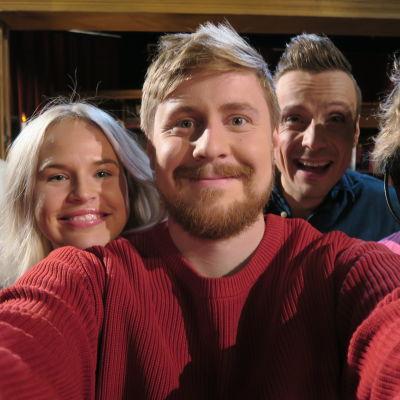 Fyra personer poserar framför kameran.