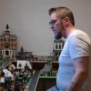 Peter Palander i en vit tshirt. Han står framför en detaljrik legostad i flera våningar.