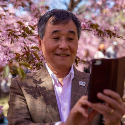 Norio Tomido, ottaa selfien Roihuvuoren kirsikkapuistossa.