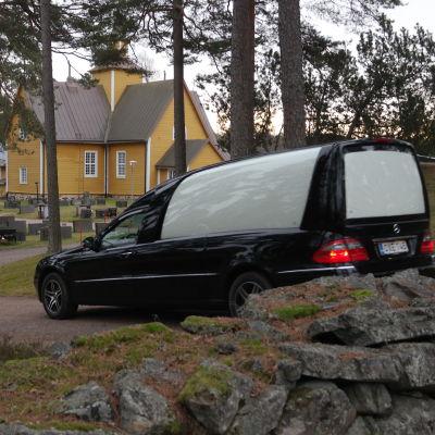 En svart begravningsbil kör in på kyrkogården i Dragsfjärd