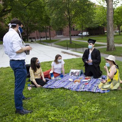 Viisi ihmisiä juhlii turvavälien etäisyydellä yliopistosta valmistunutta Harvardin edustalla murmikentällä.