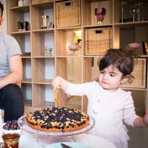 Isä ja äiti katsovat kun lapsi ottaa lusikalla mustikkapiirakkaa