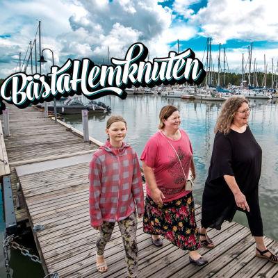 Tre personer går på en brygga med hav och segelbåtar i bakgrunden.