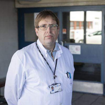 Mansperson i läkarrock står utomhus vid sjukhusentré.
