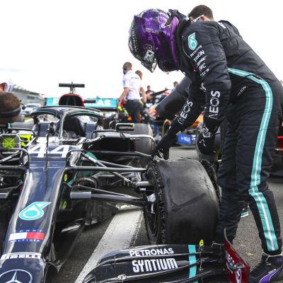 Lewis Hamilton inspekterar sitt trasiga däck.
