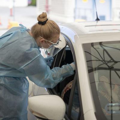 Lähihoitaja Maria Ruotsala ottaa koronanäytettä autossa istuvalta ihmiseltä.