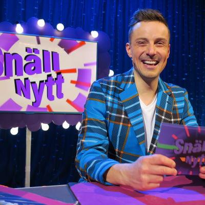 Programledaren Jontti Granbacka läser upp snällnyheter i barnprogrammet Superhjälparna