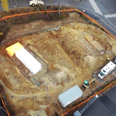 Kuvassa näkyy ylhäältä päin alue, jossa maata on kaivettu. yhden kaivauksen päällä on teltta.