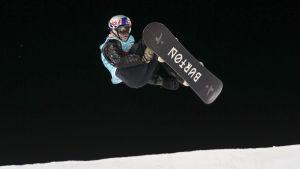Snowboardåkare i luften med nattsvart himmel i bakgrunden.