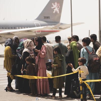 Människor står på kö till ett flygplan på flygplatsen i Kabul.