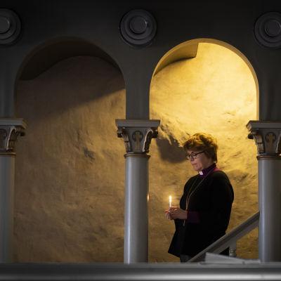 Kaisamari Hintikka kävelee portaissa kynttilä kädessä.