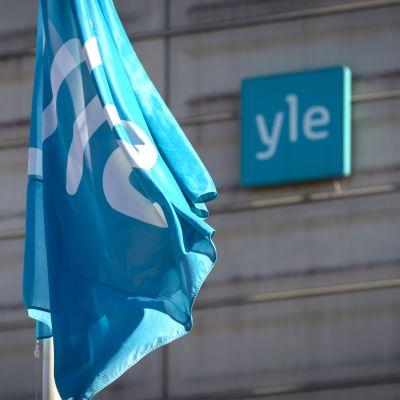 Yleisradio-logotyp på en flagga och på en gråhusvägg i bakgrunden.