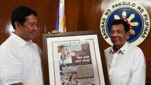 President Rodrigo Duterte (tv) emottar en dagstidnings förstasida där det står, Vi kommer inte att stoppa - en hänvvisning till Duertes omstridda kampanj Skjut för att döda