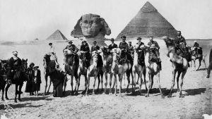 Svartvid bild av sällskap på kameler vid pyramiderna. På bilden syns bland nadra Gertrude Bell flankerad av Winston Churchill och T.E. Lawrence.
