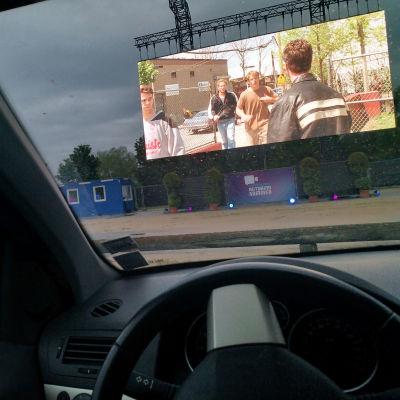 Skärmen vid en drive-in-biograf sedd inifrån en bil.