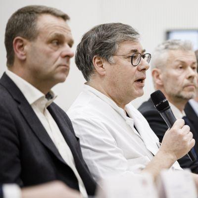 Fyra män fotograferade från sidan. En av dem är klädd i en vit läkarrock och håller i en mikrofon. De övriga tittar framåt.