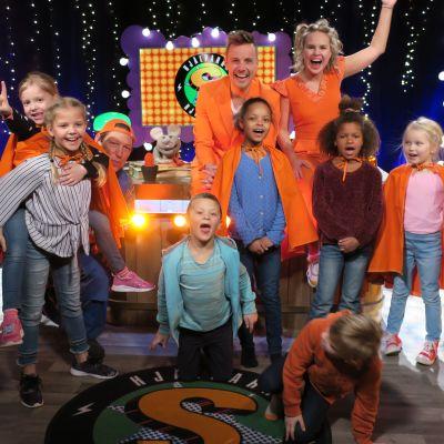 Programledarna Jontti och Malin sitter på skrivbordet i superhjälparstudion och har flera barn runt sig. Alla ser glada ut.