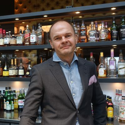 Pekka Tyynilä i kavaj står bakom en bardisk med en hylla med spritflaskor i bakgrunden