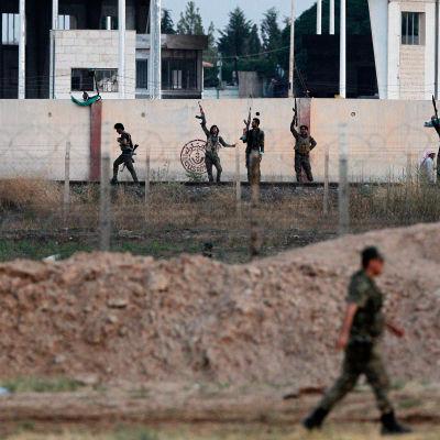 Soldater i Fria syriska armén i bakgrunden, fotograferade från den turkiska sidan av gränsen mellan länderna.