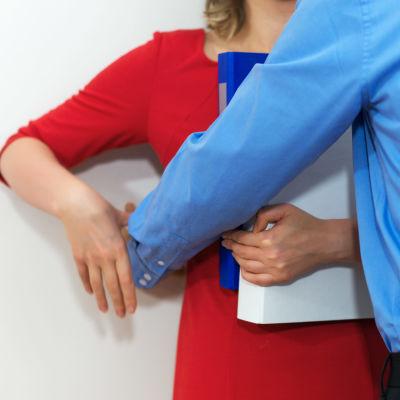 En kvinna står lutad mot en vägg och en man står framför henne.