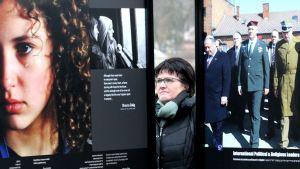 """Besökare tittar på bilder i utställningen """"March of the Living"""" utanför lägren i Auschwitz."""