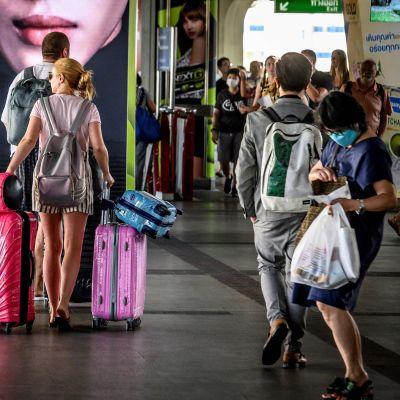 Turistfamilj med många kappsäckar i Bangkok.
