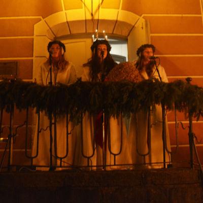 Lucia och två tärnor står utomhus på en trappa och sjunger i mikrofoner.