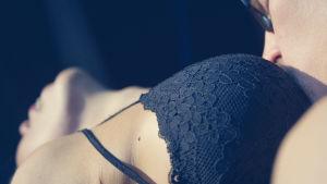Mies suutelee naisen rintojen väliä