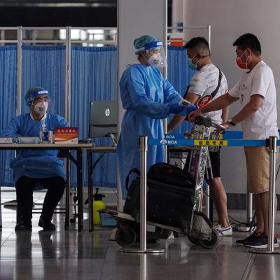 Suojapukuun pukeutunut ihminen mittaa ruumiinlämpöä matkatavaroidensa vieressä seisovalta matkustajalta.