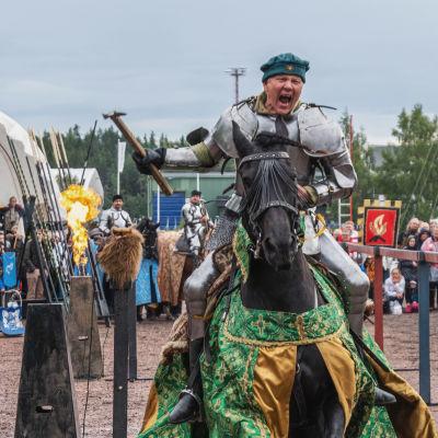 Ritari ratsastaa hevosella turnajaisissa kädessään vasara ja huutaa. Taustalla areena ja yleisöä.