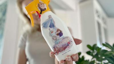 En kvinna står och håller fram en flaska med solkräm som skymmer hennes ansikte. På flaskan finns fastlimmade klistermärken på Frozen-karaktärer.