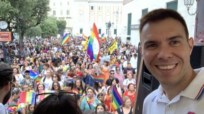 En man ler mot kameran. Bakom honom firar människor pride.