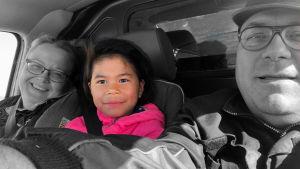 Familjen Nordmyr selfie i bil. Svartvit bild där dottern Samantha är i färg.