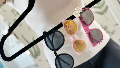 En kvinna håller i en svart klädhängare där en tre par solglasögon hänger på rad. Solglasögonen är i fokus och bara kvinnans båle syns.