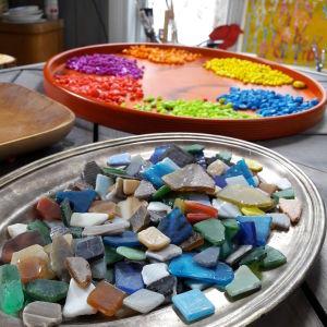 Mosaikstenar på en bricka och mosaikglasbitar.