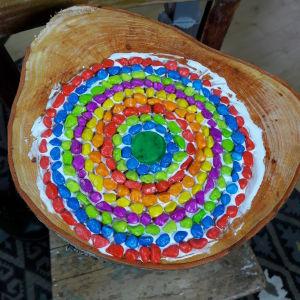 Mosaikstenar i olika färger limmade på en stubbe