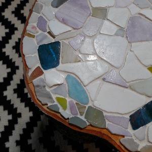 Ytan på mosaikstubbe med mosaik som är fästa med lim på bordsytan.