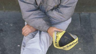 Köyhä mies istuu maassa kerjäämässä rahaa lippalakkiinsa (1991)