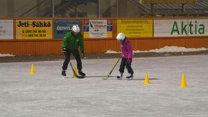 En tjej tränar på att dribbla mellan gula koner på isen.