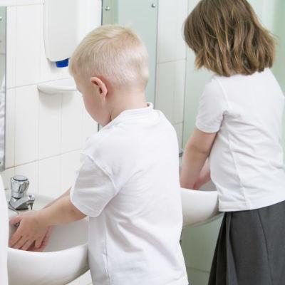 Tre barn står vid varsin lavoar och tvättar sina händer.