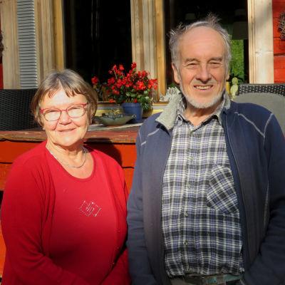 En äldre kvinna och äldre man står framför en rödmålad stockstuga. De ser in i kameran och ler.
