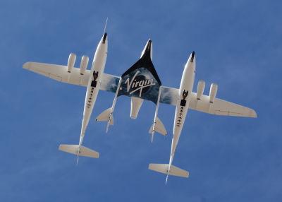 """Rymdflygplanet SpaceShipTwo sedd underifrån, under vingarna på """"moderfarkosten"""" VNS Eve."""