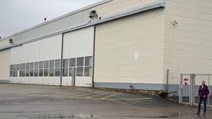 Gun Gustavsson framför en hangar