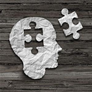 Ett pappershuvud som saknar en bit i form av ett pussel och matchande pusselbit ligger bredvid.