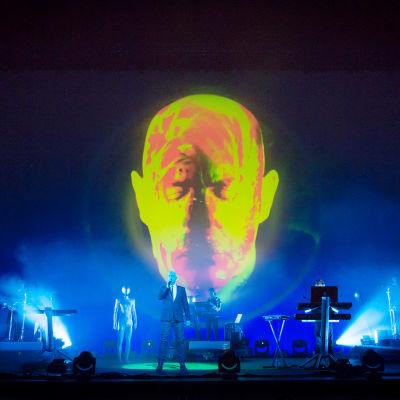 Pet Shop Boys lavalla, taustalla iso valaistu pää.