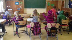 Elever sitter i ett klassrum med stolar och pulpeter