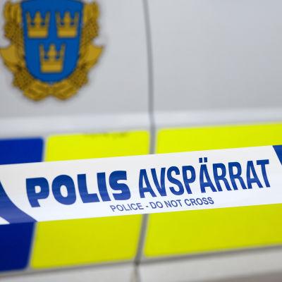 """Närbild på platsband där det står """"polis avspärrat"""" framför en svensk polisbil."""