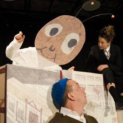 På bilden en scen ur föreställningen Sailor & Pekka där en tapetförsäljare talar till Sailor och Pekka.