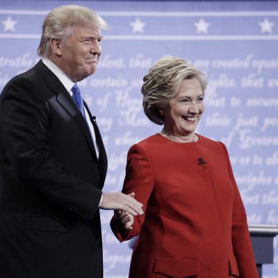 Donald Trump ja Hillary Clinton kättelevät ja hymyilevät.