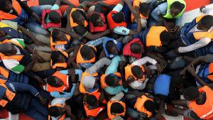 Flyktingar i flytvästar på en båt på Medelhavet.